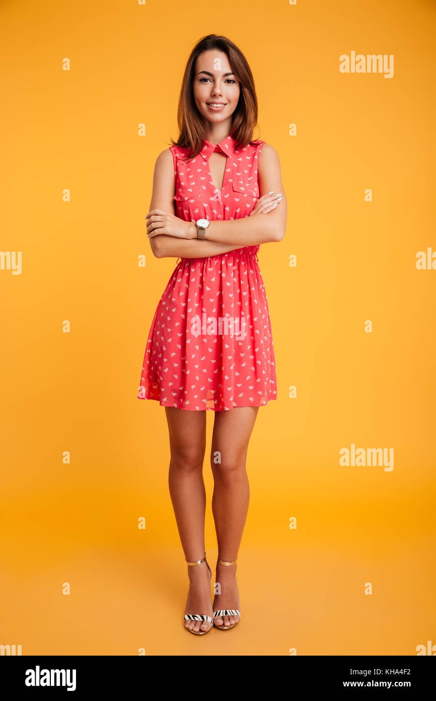 Full length pfoto of beautiful smiling woman standing with crossed hands, looking at camera, isolated on yellow - Stock Image
