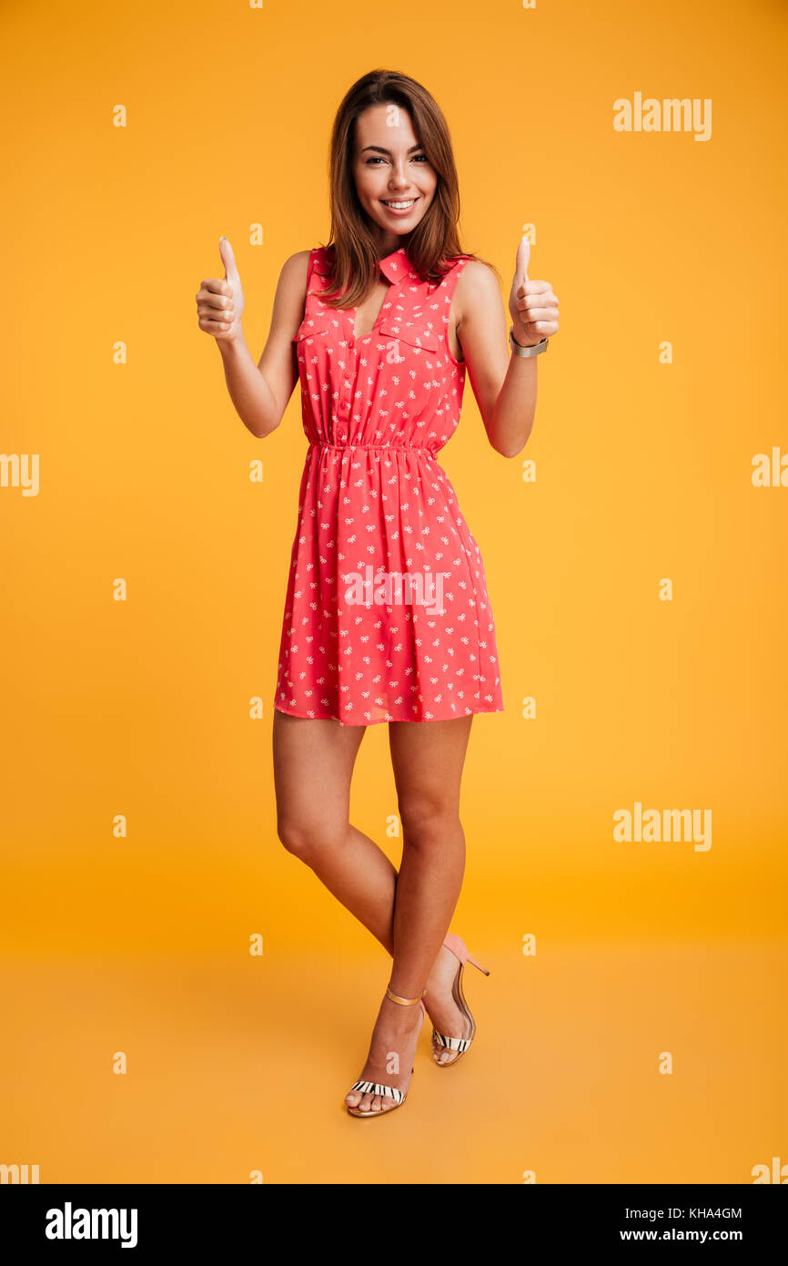 Full-length portrait of young happy woman standing with crossed legs showing thumbs up gesture, looking at camera, - Stock Image