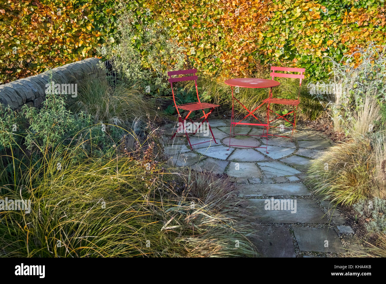 Small garden patio area with paving slabs and dining table and chairs, autumn, England, UK Stock Photo