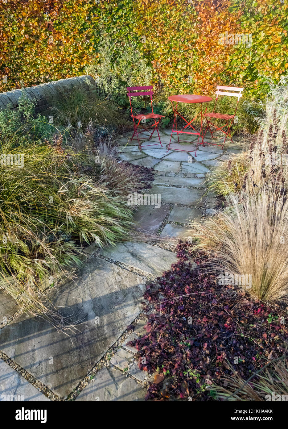 Small garden patio area with paving slabs, dining table and chairs, and autumn colour plants foliage, England, UK Stock Photo