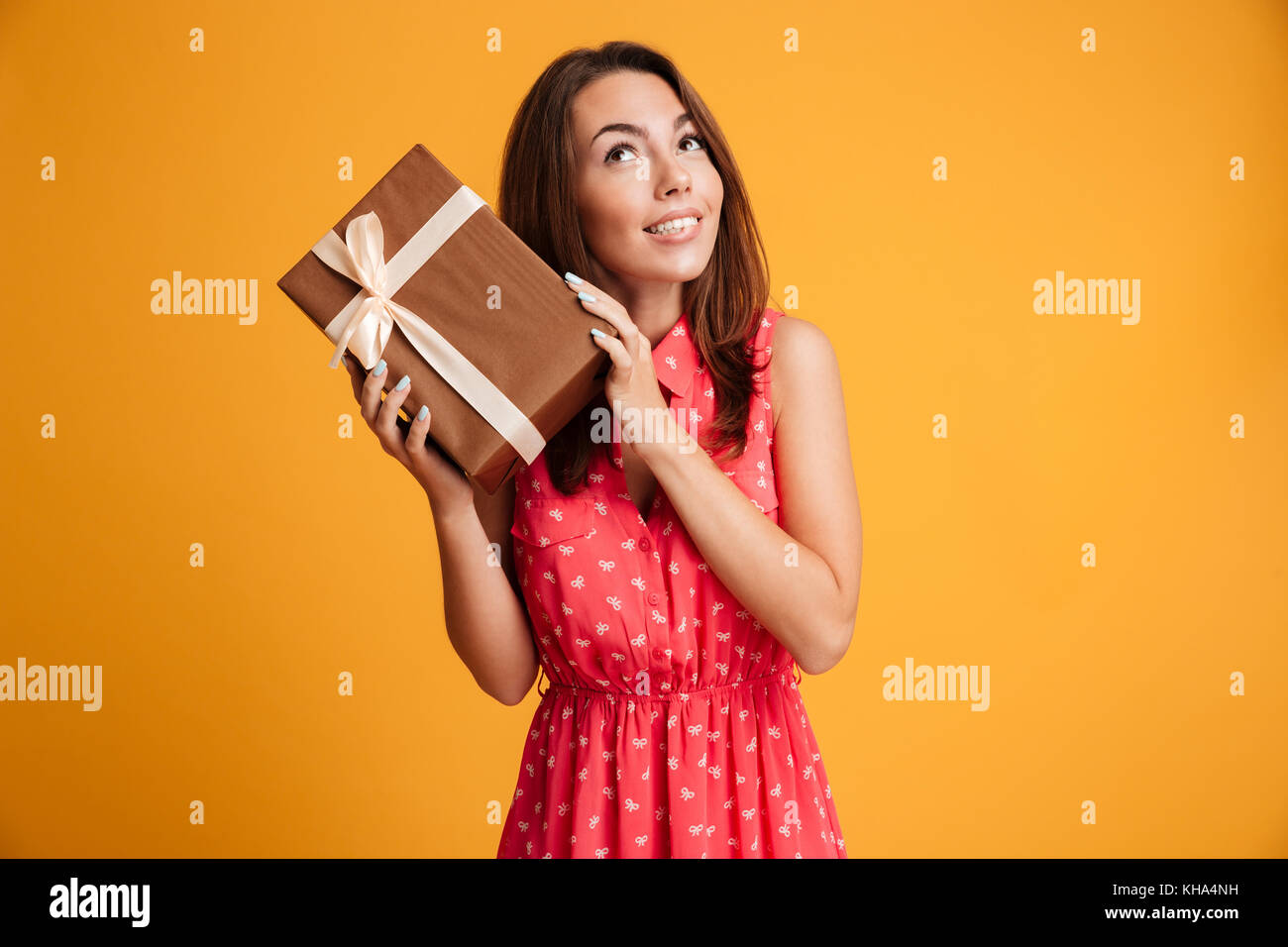 Intrigued runette woman in dress holding gift and looking up over yellow background - Stock Image