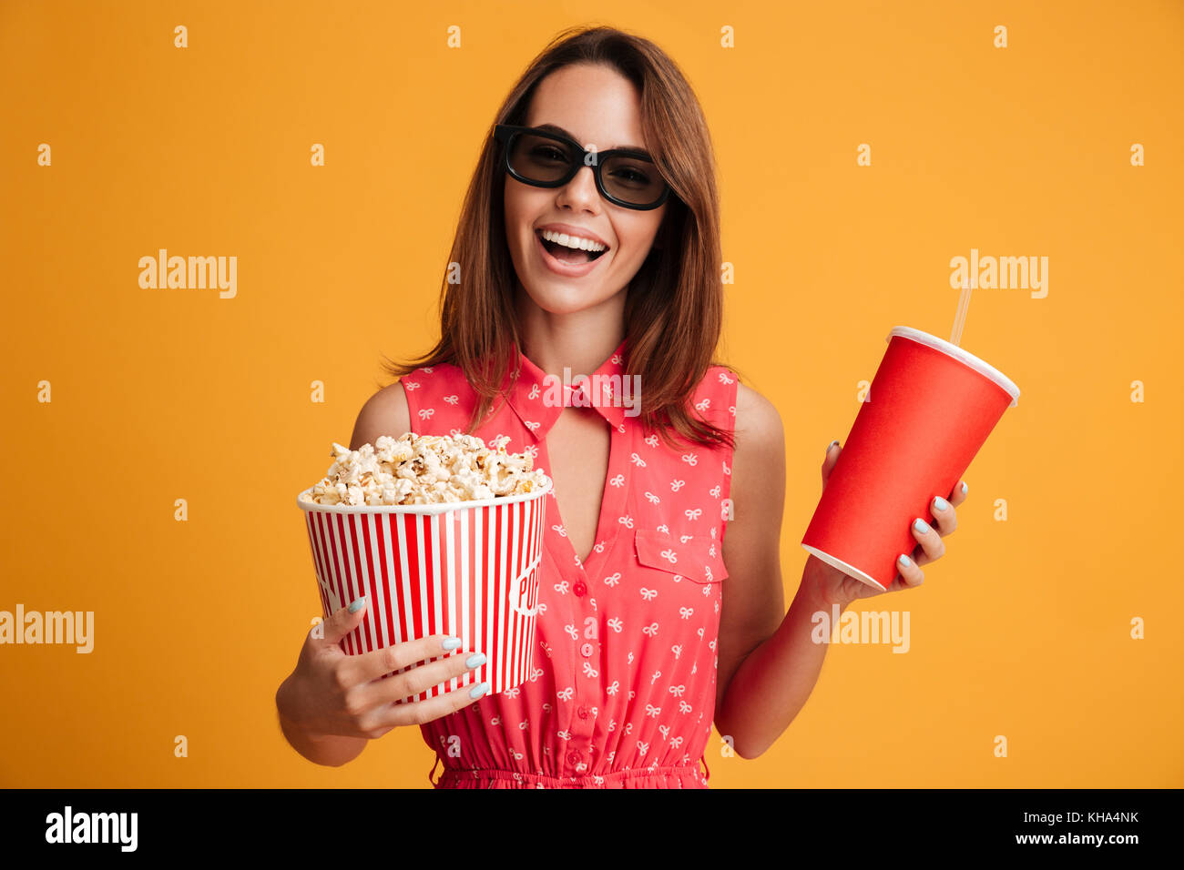 Happy brunette woman in dress and eyeglasses preparing to watch the film while holding popcorn and soda over yellow background Stock Photo