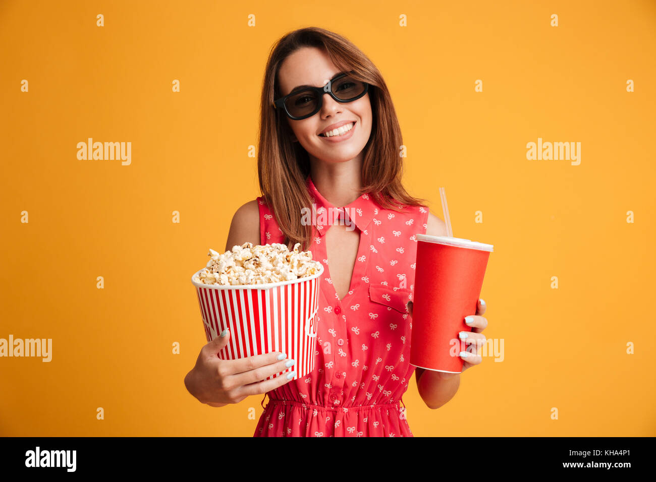 Pleased brunette woman in dress and eyeglasses preparing to watch the film while holding popcorn and soda over yellow background Stock Photo