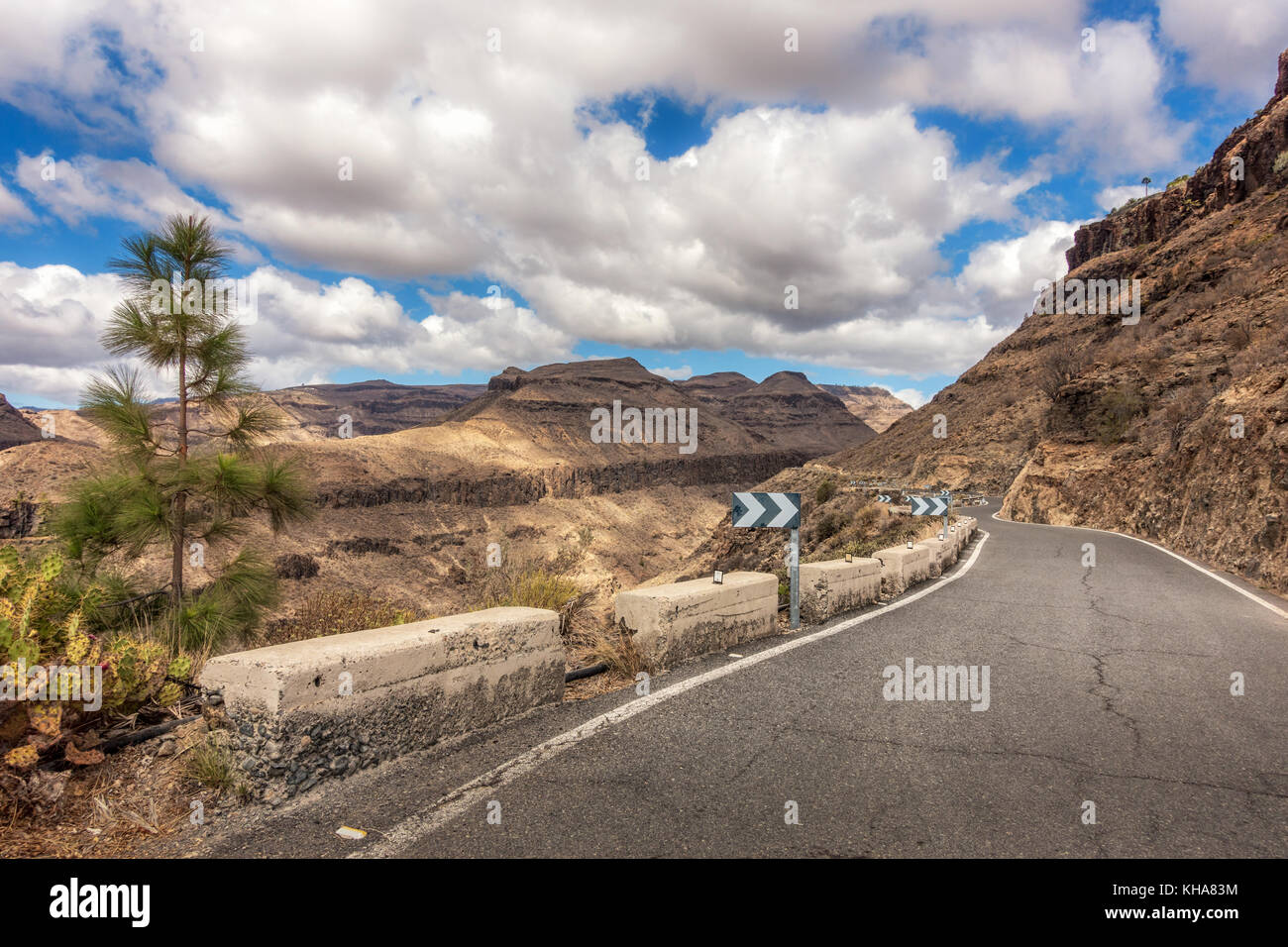 Mountain views inland of an empty road on the descent from Ayagaures, Gran Canaria, Canary Islands, Spain - Stock Image