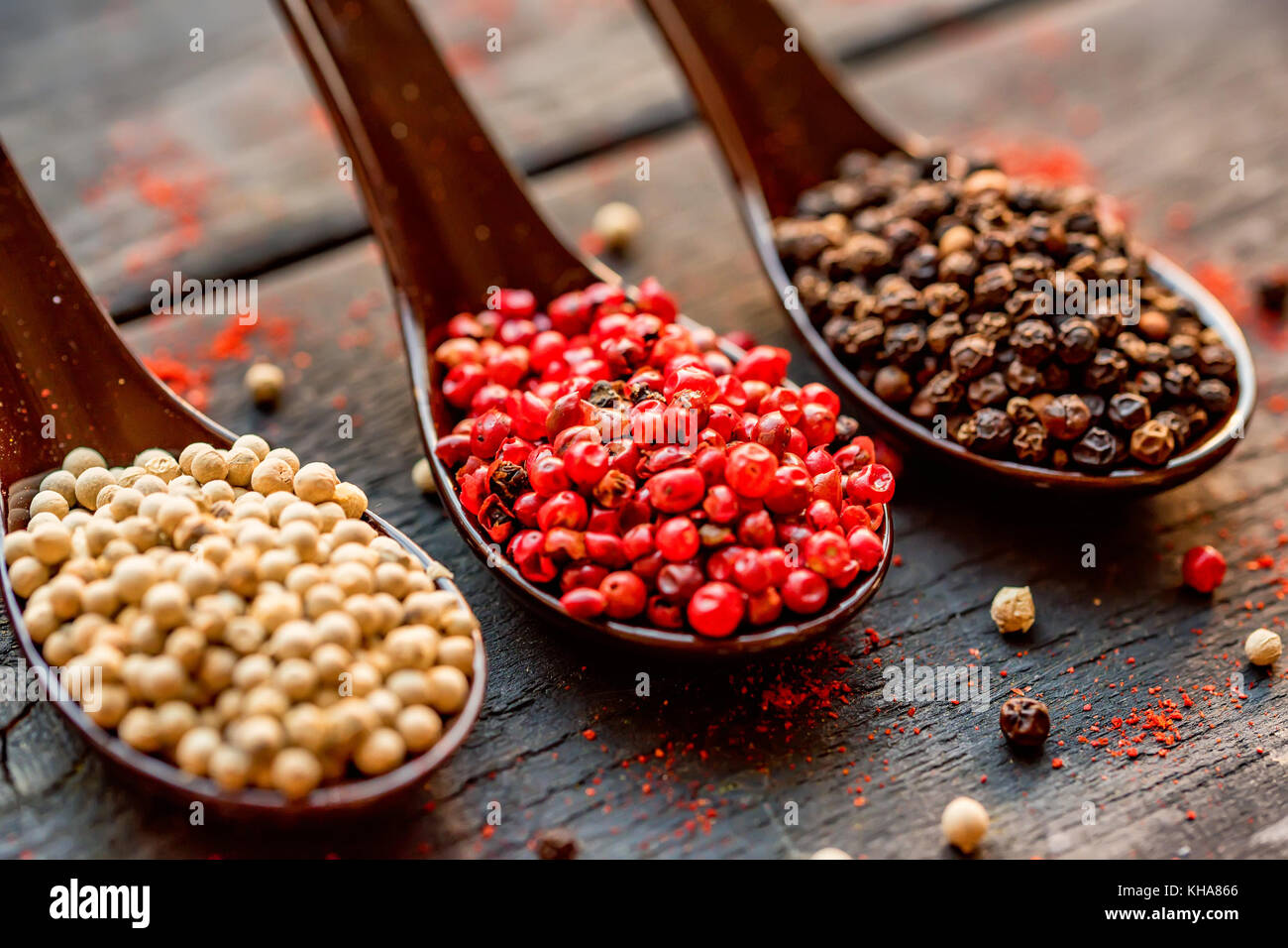Three spoons with black, pink and white peppercorn - Stock Image