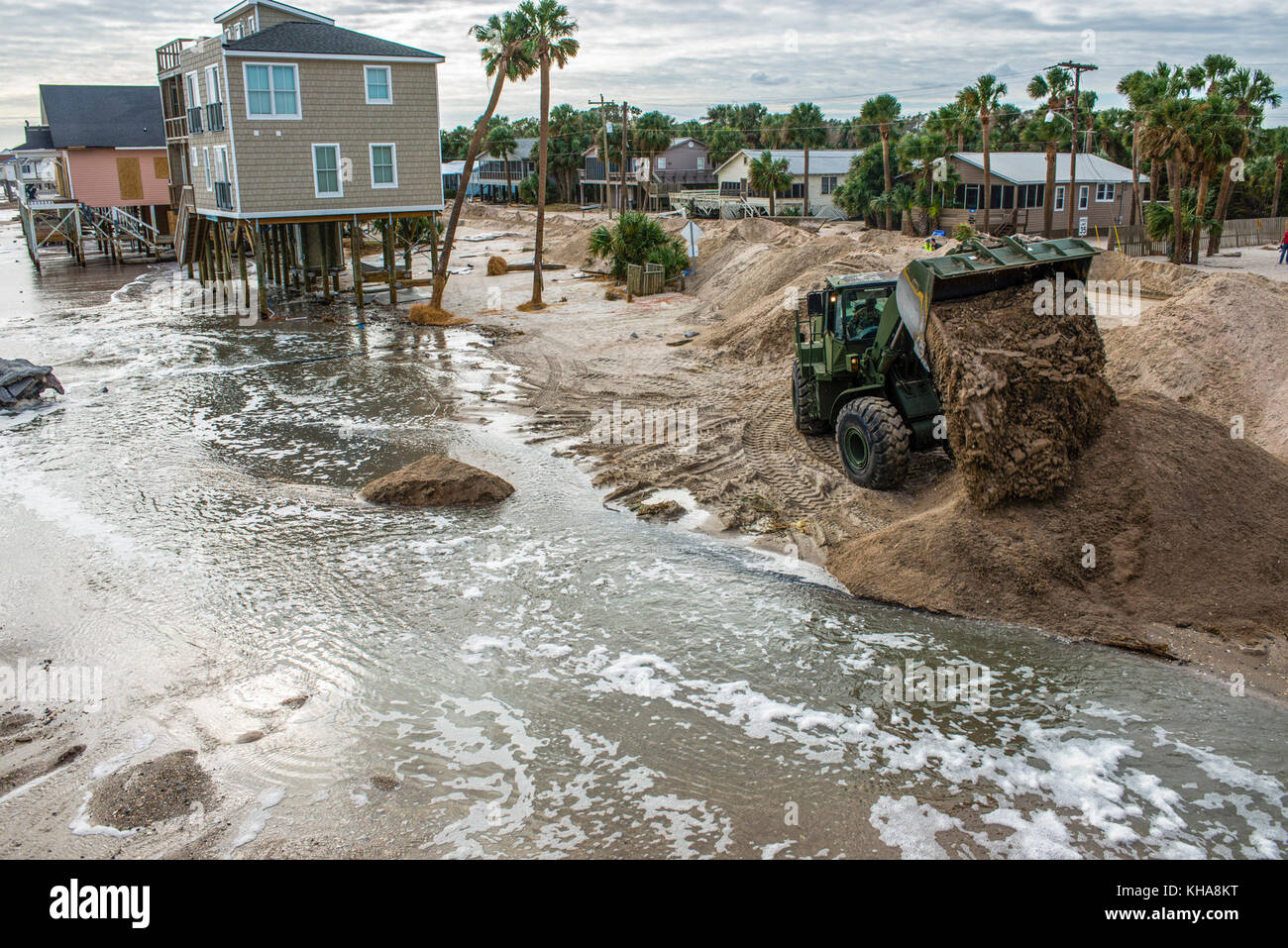 A member of the South Carolina Army National Guard dumps sand while cleaning up after Hurricane Matthew at Edisto - Stock Image