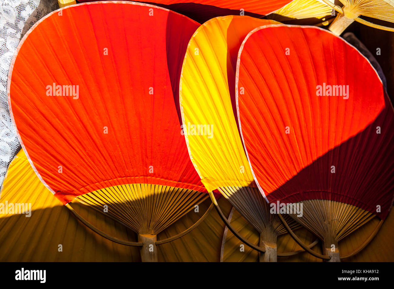 5078ff3c7115d Setting of handheld fans for wedding guests. Red and yellow bamboo rigid  fans - Stock