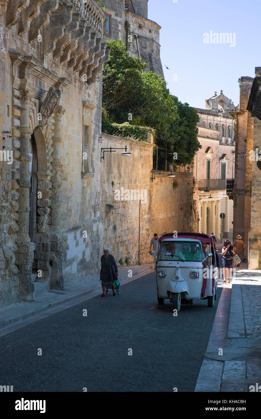A Piaggio Ape 3-wheeler climbs the hill, Via Duomo in La Civita, Matera, Basilicata, Italy - Stock Image