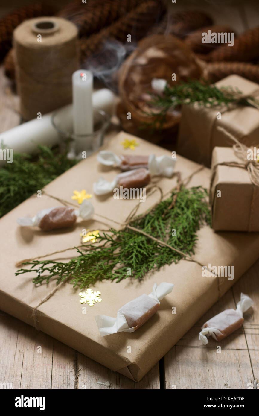 Gifts and homemade toffee in Christmas decorations. Rustic style, selective focus.