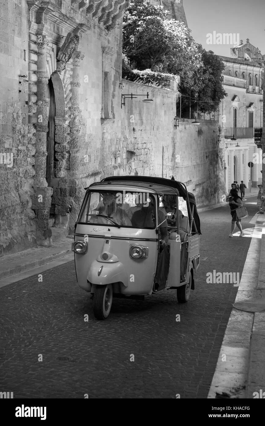 Piaggio 'Ape' 3-wheeler taxi on Via Duomo in La Civita, Matera, Basilicata, Italy: black and white version - Stock Image
