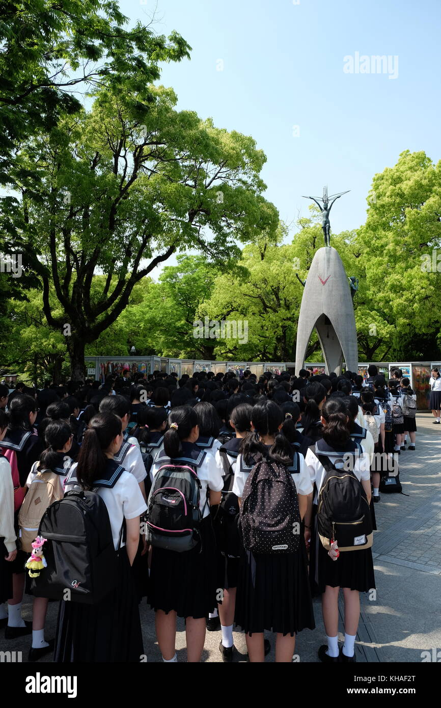 Japanese school children in uniform singing in front of the Children's Peace Monument in Hiroshima, Japan. - Stock Image