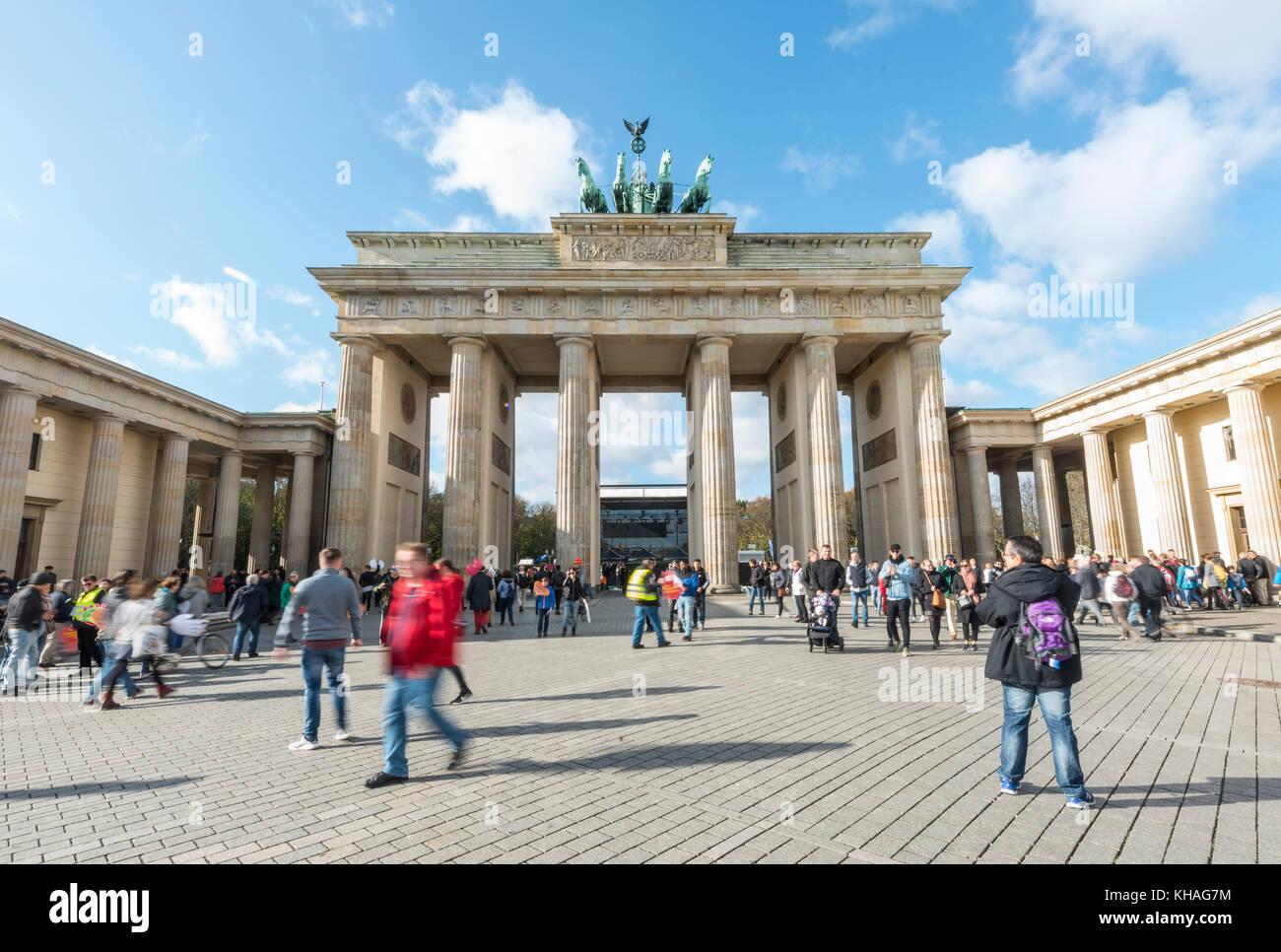 People run across the square at Brandenburg Gate, Berlin, Germany - Stock Image