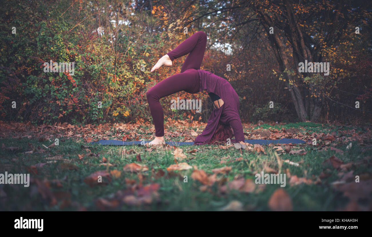 Girl on an autumn day practicing yoga outdoors, doing variation of one-legged inverted staff pose (eka pada viparita - Stock Image