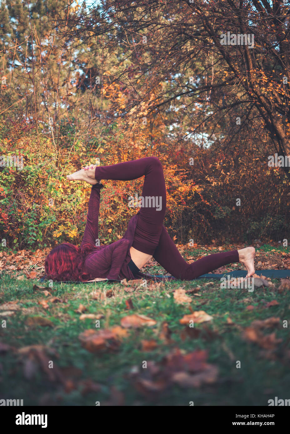 Girl on a bright autumn day practicing yoga outdoors, doing variation of one-legged eight-limbed pose (eka pada - Stock Image