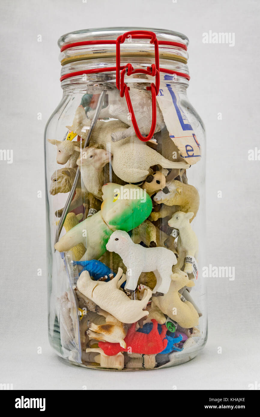 Glass jar of small lamb collectibles - Stock Image