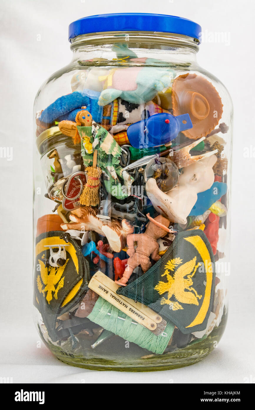 Glass jar of small miscellaneous collectibles - Stock Image