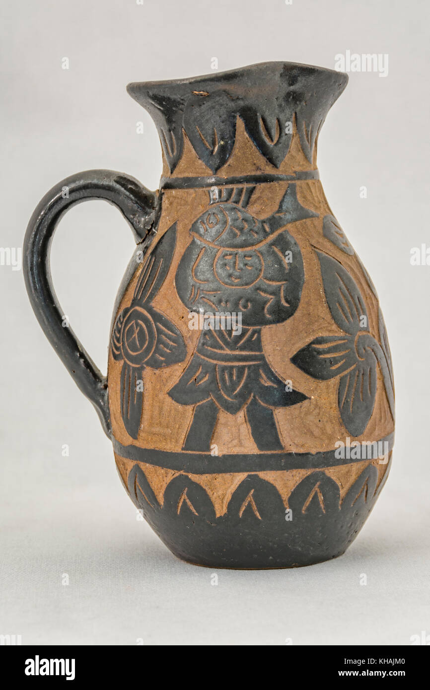 Brown and black clay pottery from Okinawa with fish, man, and flowers - Stock Image