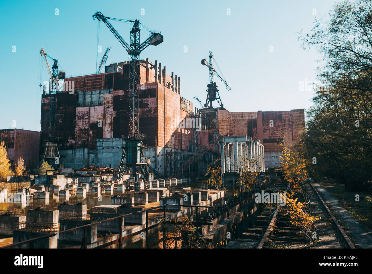An incomplete building construction lies in ruins near the Chernobyl power plant, Ukraine - Stock Image
