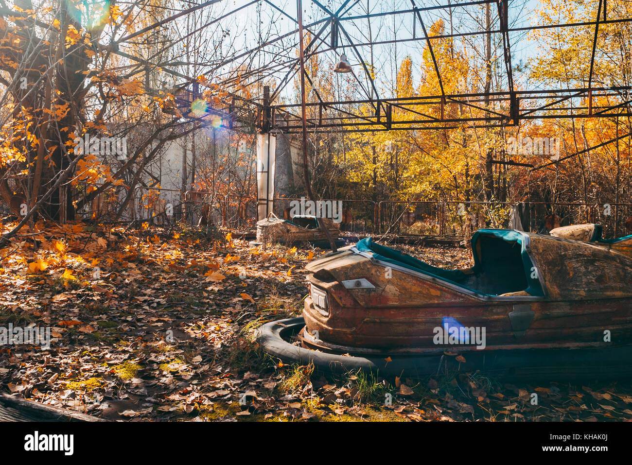 A forgotten bumper car lies amongst autumn leaves in the infamous abandoned theme park in Pripyat, near Chernobyl, - Stock Image