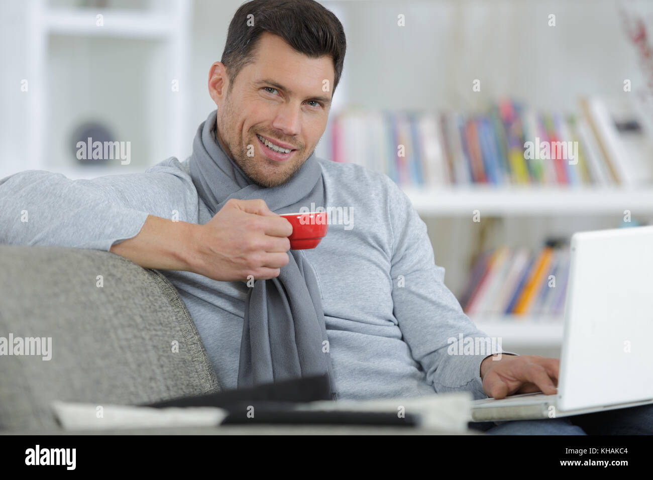 handsome man drinking coffee while working with laptop at home - Stock Image