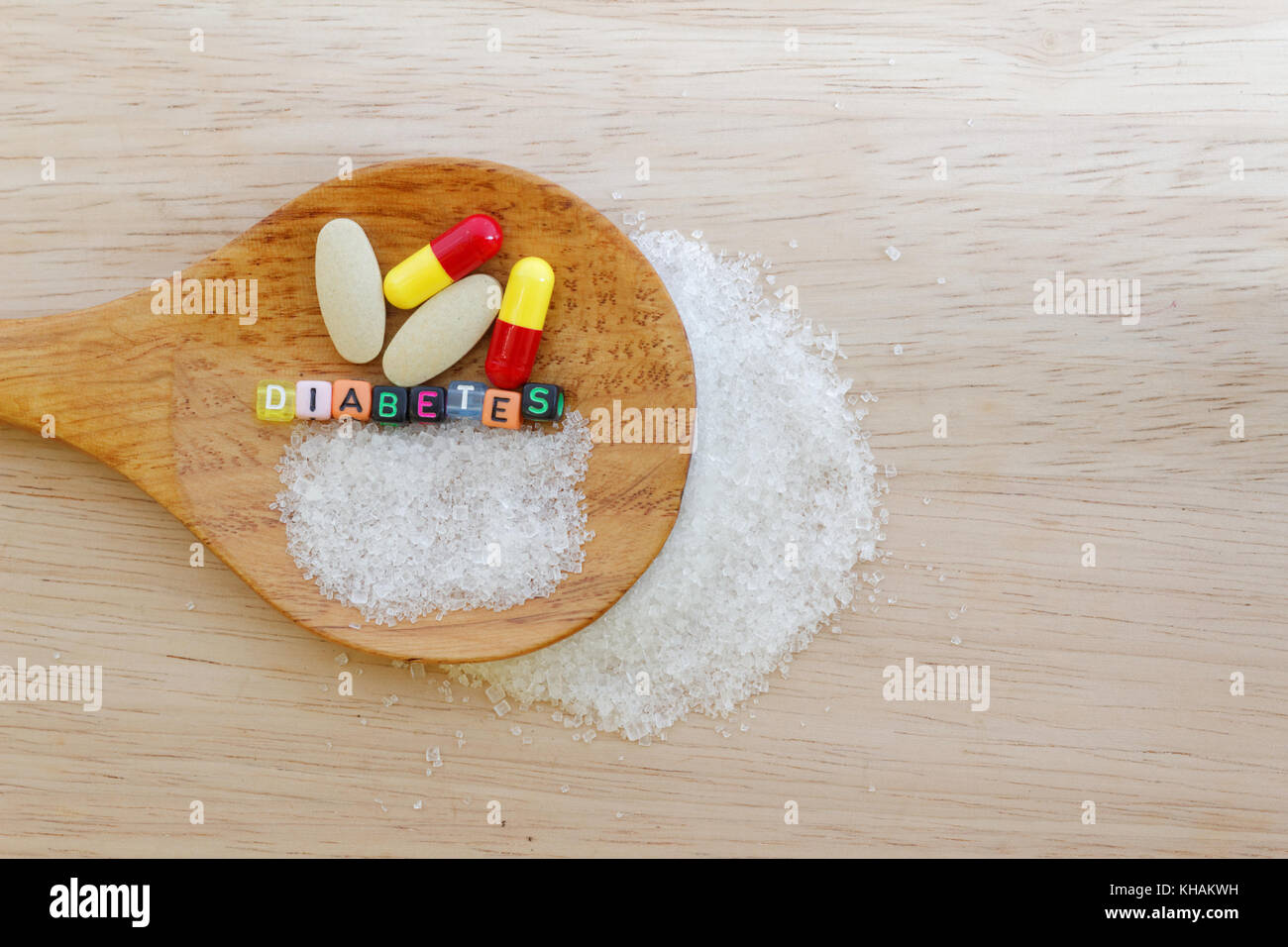 Medicine and the word Diabetes and sugar in spatula on wooden background - Stock Image