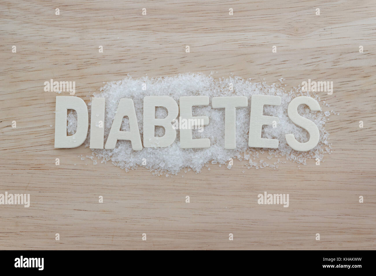 Diabetes concept. Alphabet with word DIABETES with sugar on wooden background. - Stock Image