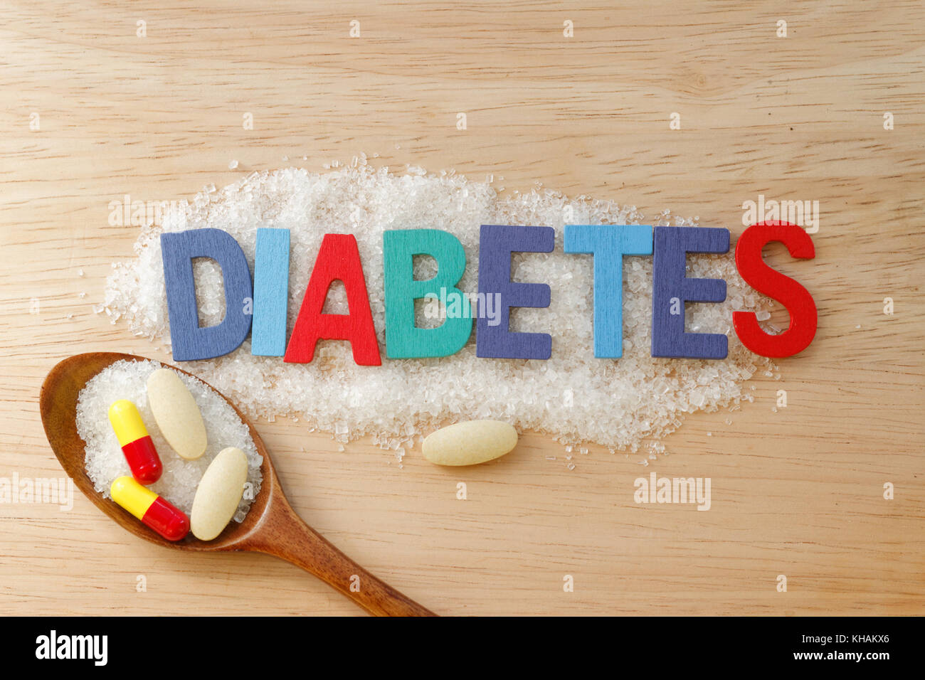Diabetes concept. Colorful / colourful alphabet with word DIABETES with sugar and pills on wooden background. - Stock Image