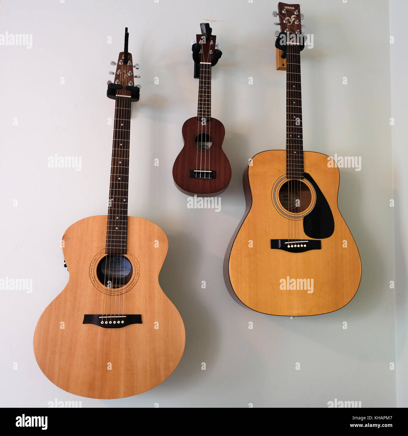 Two guitars and one banjo hanging on wall in symmetrical placement of musical instruments - Stock Image