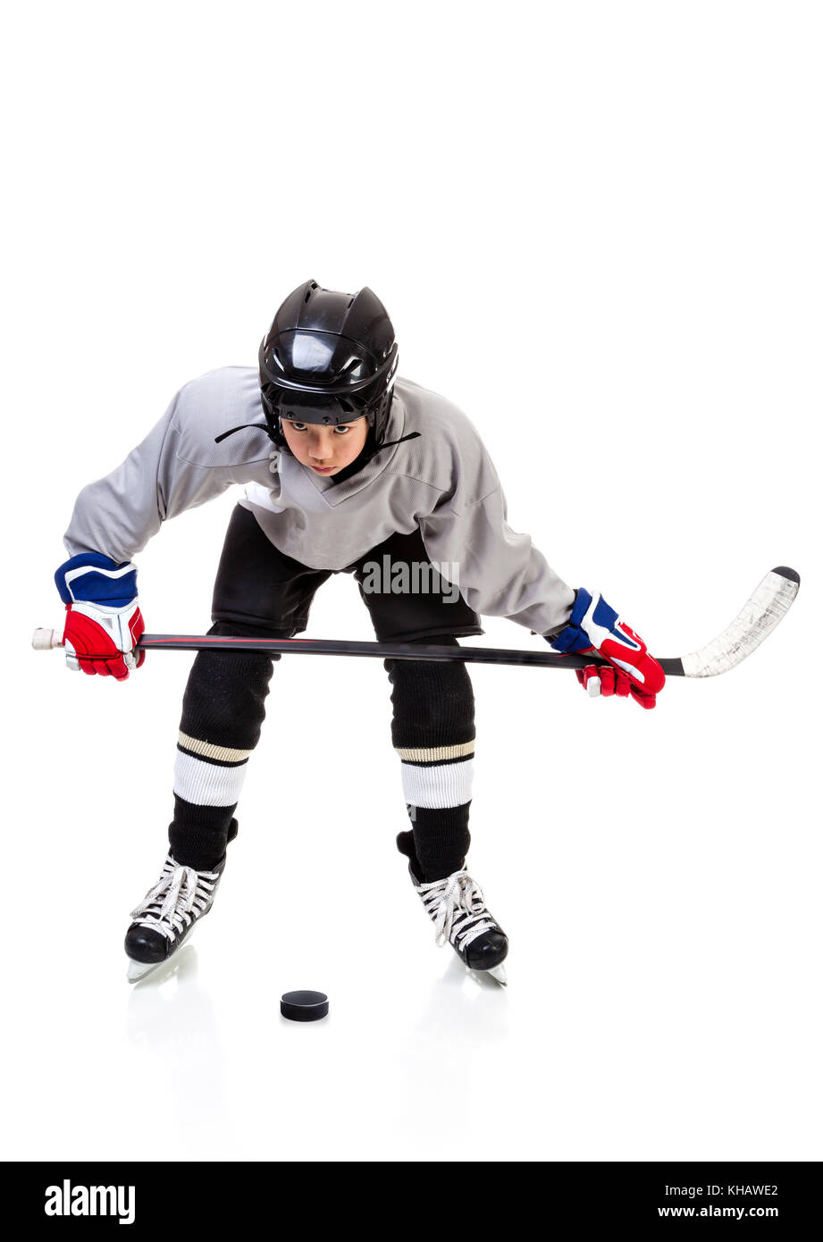 Junior ice hockey player with full equipment and uniform isolated on white background. In faceoff stance with hockey - Stock Image