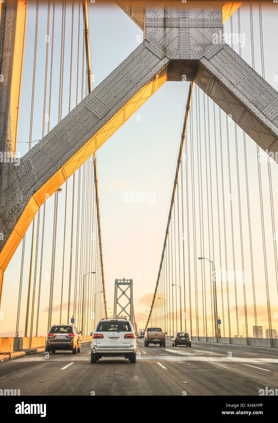 The bay bridge lit up at sunset while cars drive over the bay bridge into San Francisco from the east bay. 260,000 - Stock Image