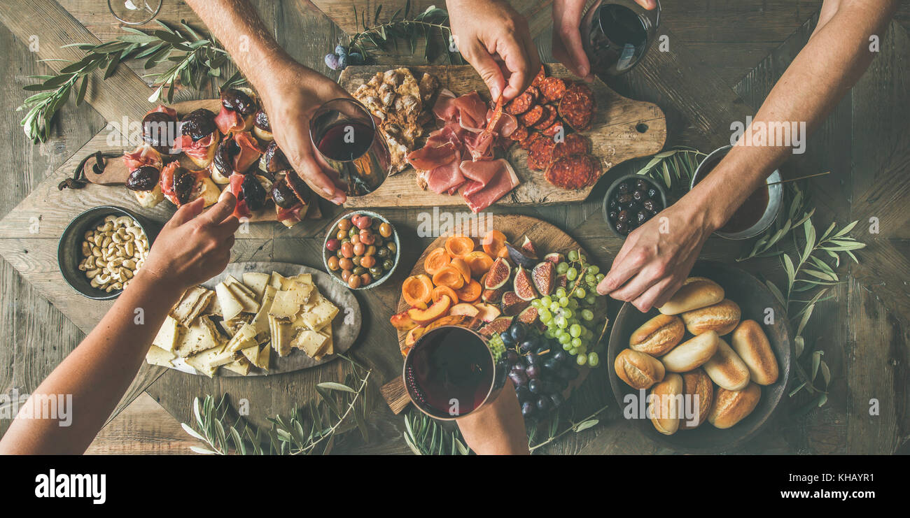 Top view of people drinking, eating together and holding glasses Stock Photo