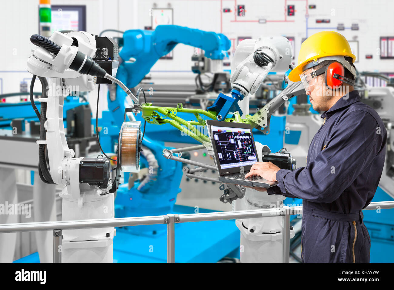 Engineer using laptop computer maintenance automatic robotic welding with robot workpiece in automotive industry, - Stock Image
