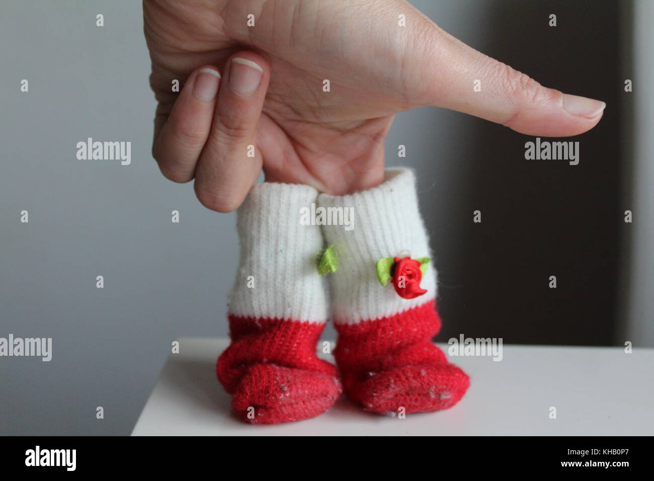 red and white sock in hands - Stock Image