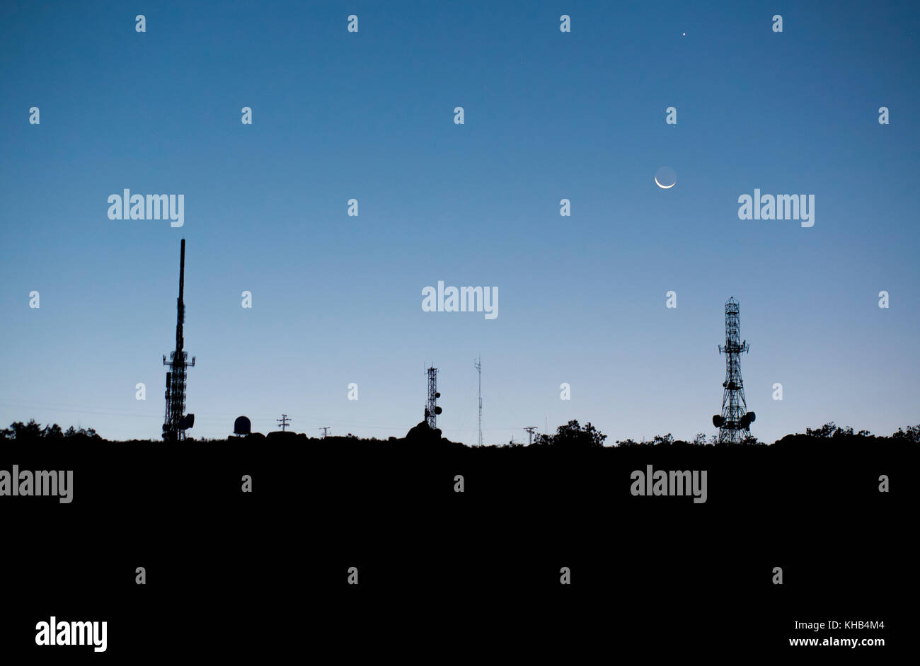 Broadcast relay station antennas at rising. Moon and the planets Venus and Mars form a conjunction in the sky just - Stock Image
