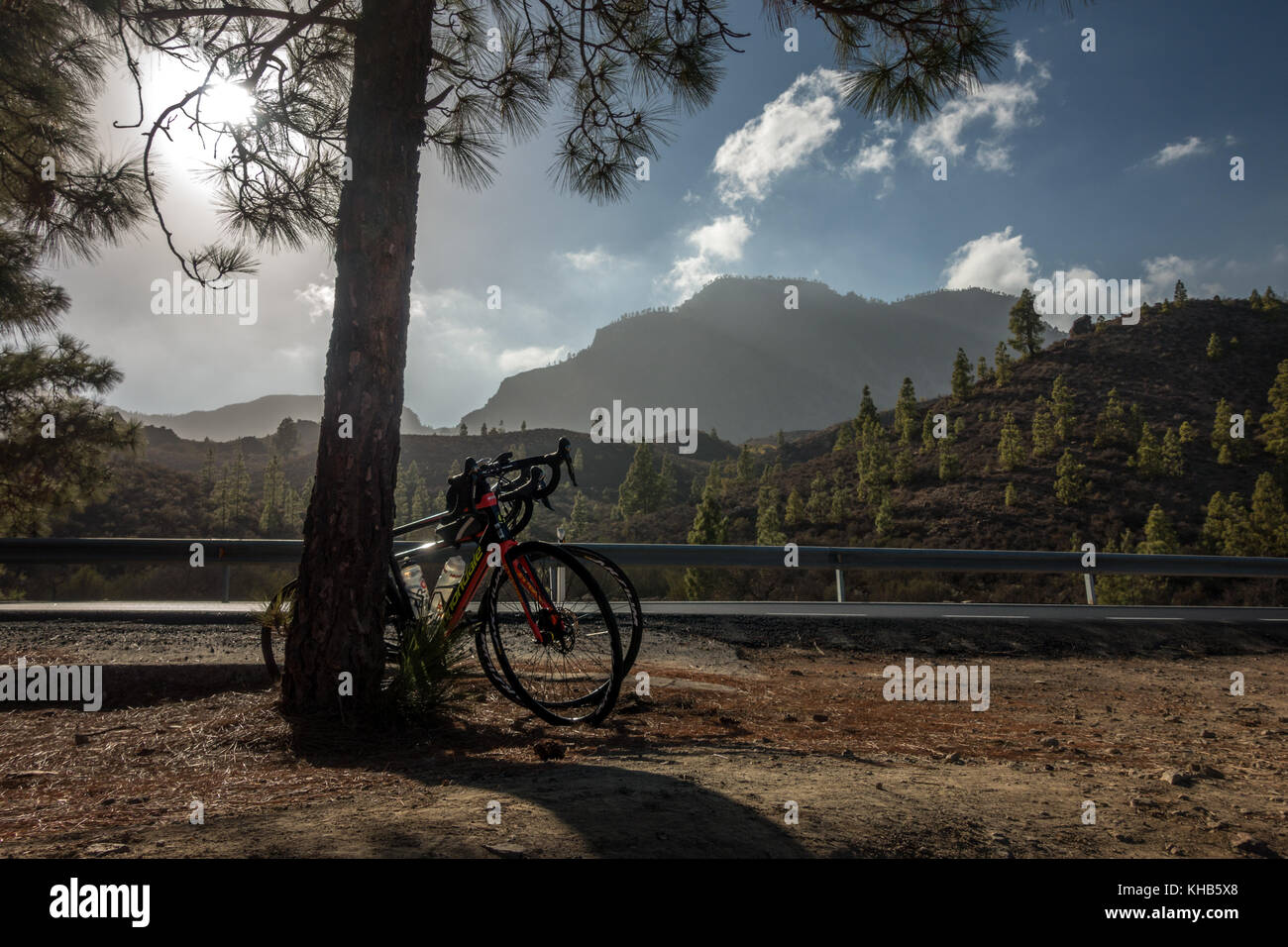 Mountain views inland with two bikes resting against a tree next to the road, Gran Canaria, Canary Islands - Stock Image