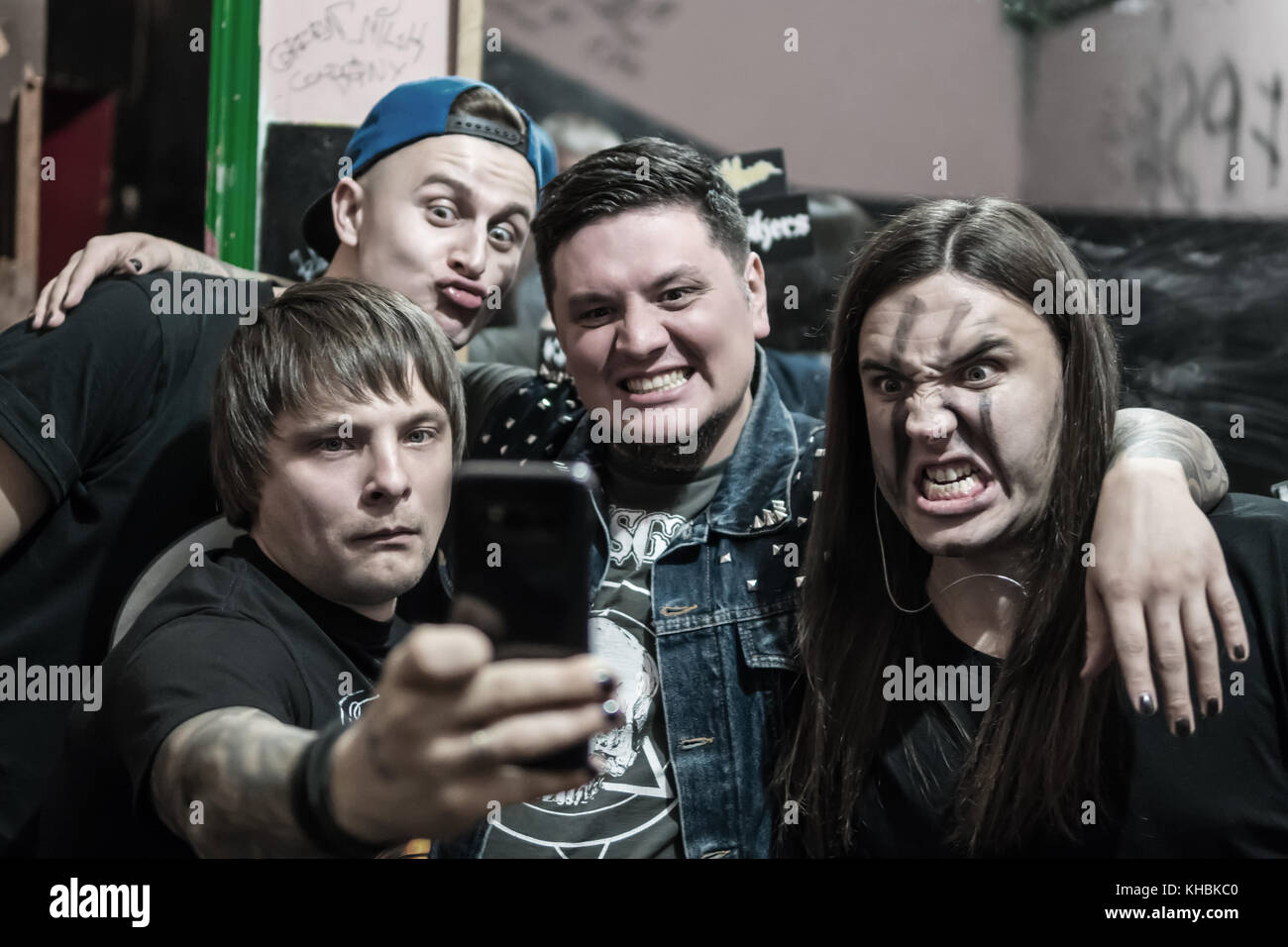 Group of men do selfie in a dark room, grimacing before the camera - Stock Image