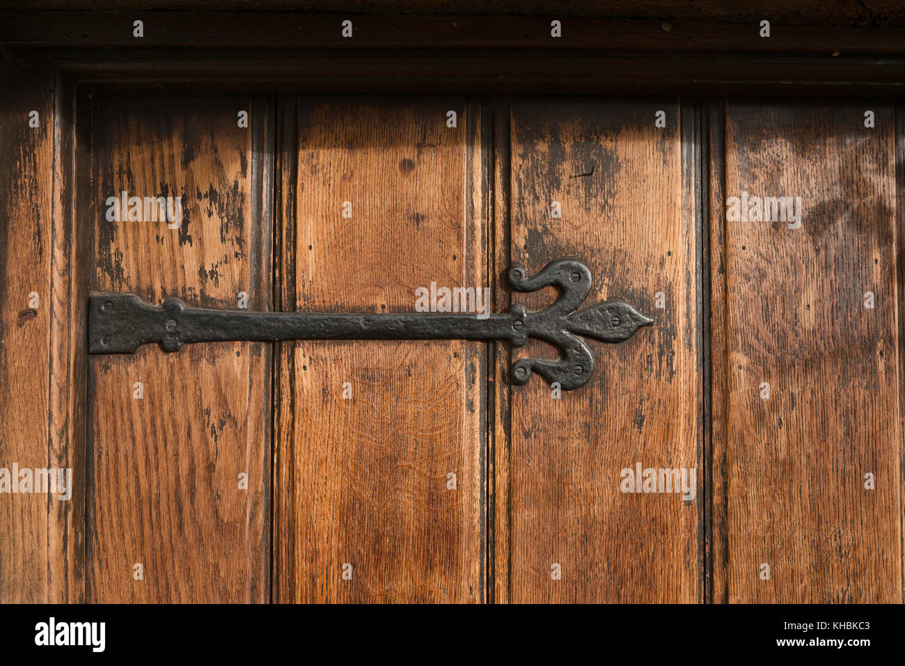 A substantial black cast iron, ornate, antique hinge fitted to an aged, tongue & groove oak front door. - Stock Image