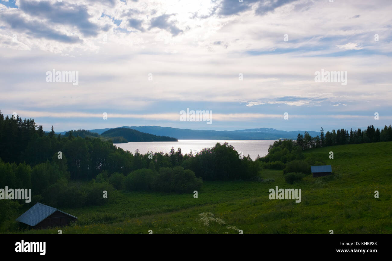 a sunny view of a lake and field in northern Sweden Europe during a calm summerday - Stock Image