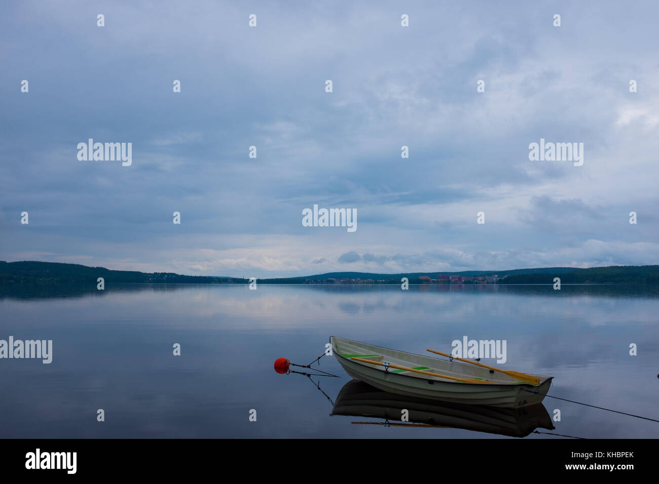A moored rowboat by a calm lake in northern Sweden - Stock Image