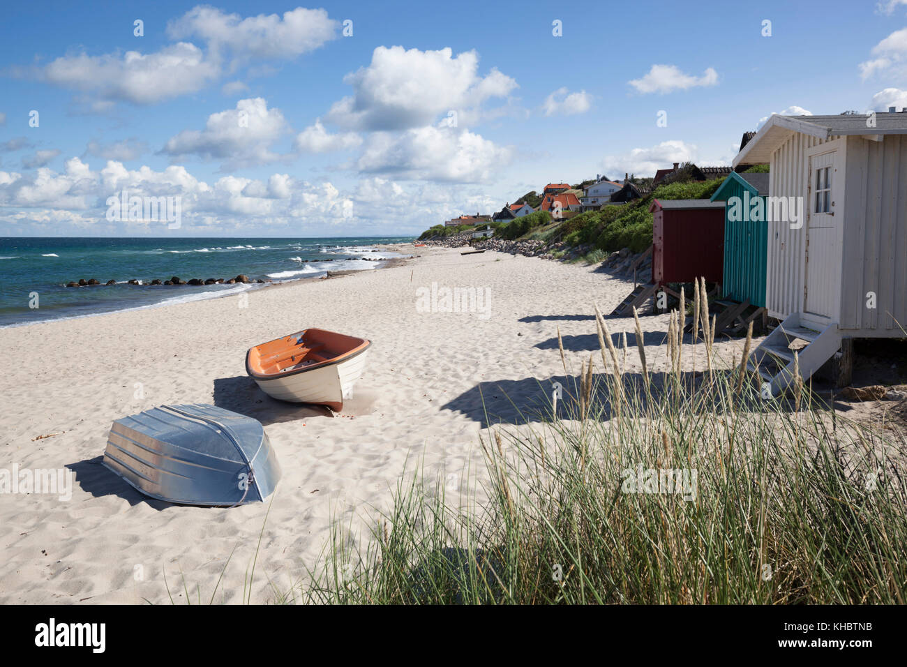 Boats and beach huts on white sand beach with town behind, Tisvilde, Kattegat Coast, Zealand, Denmark, Europe - Stock Image