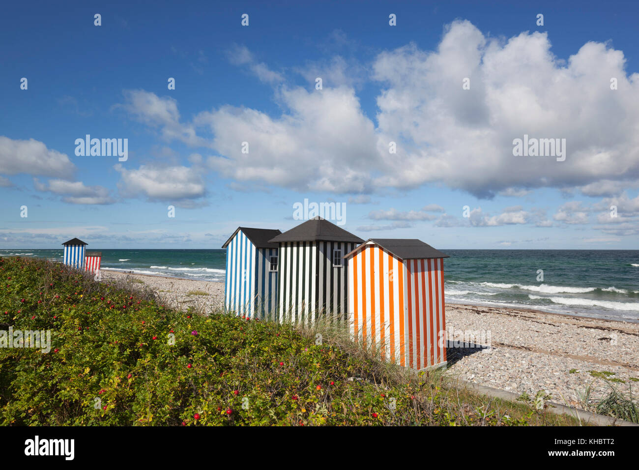 Colourful beach huts on pebble beach with blue sea and sky with clouds, Rageleje, Kattegat Coast, Zealand, Denmark, - Stock Image