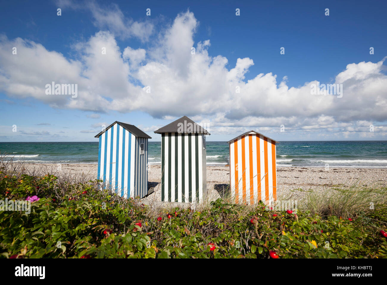 Colourful beach huts on pebble beach with blue sea and sky with clouds, Rageleje Strand, Kattegat Coast, Zealand, - Stock Image