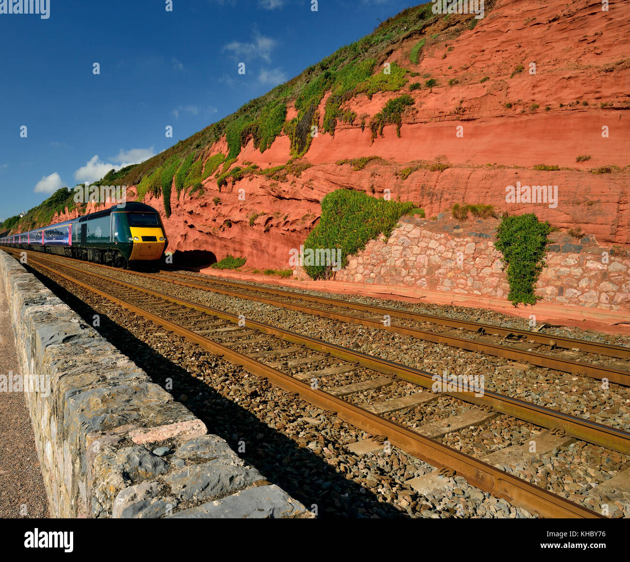 Red sandstone cliffs beside the railway and sea wall at Dawlish. - Stock Image