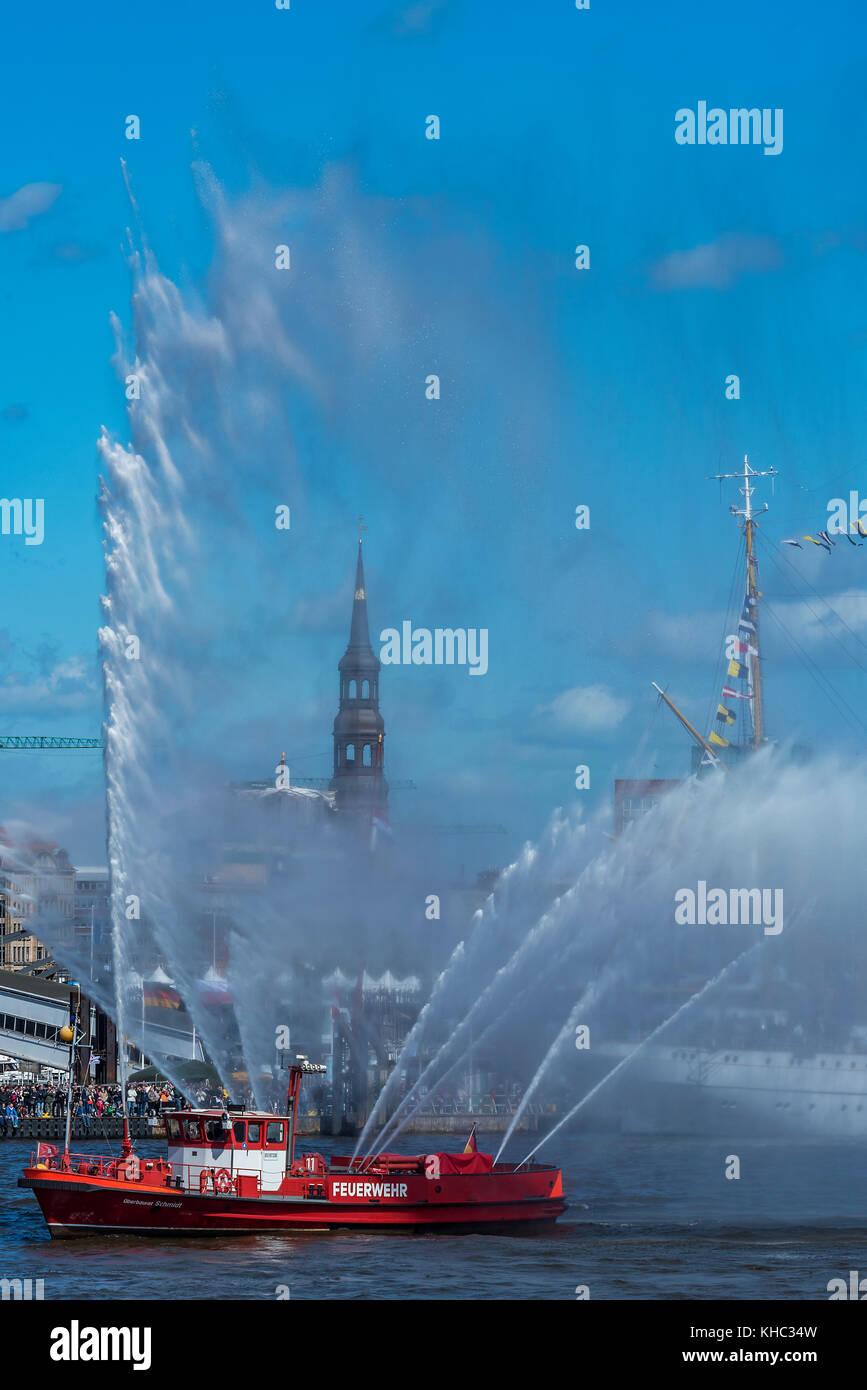 Die Katharinenkirche in Hamburg zwischen den Wasserfontänen eines Feuerwehrschiffs beim Hafengeburtstag - Stock Image