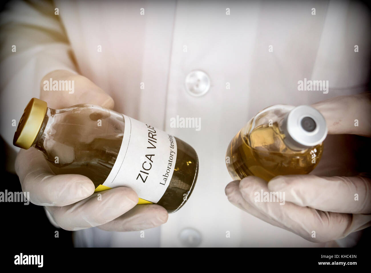 Doctor holds a sample vial of Zika virus in a hospital. Conceptual image - Stock Image