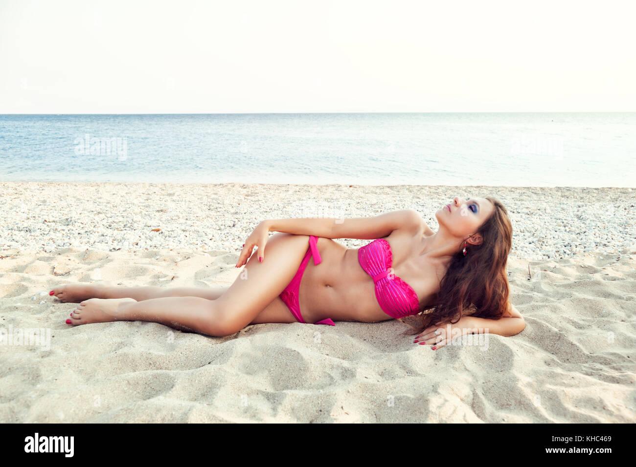 643677319f0 Girl in hot pink bikini on beautiful white sandy beach. - Stock Image