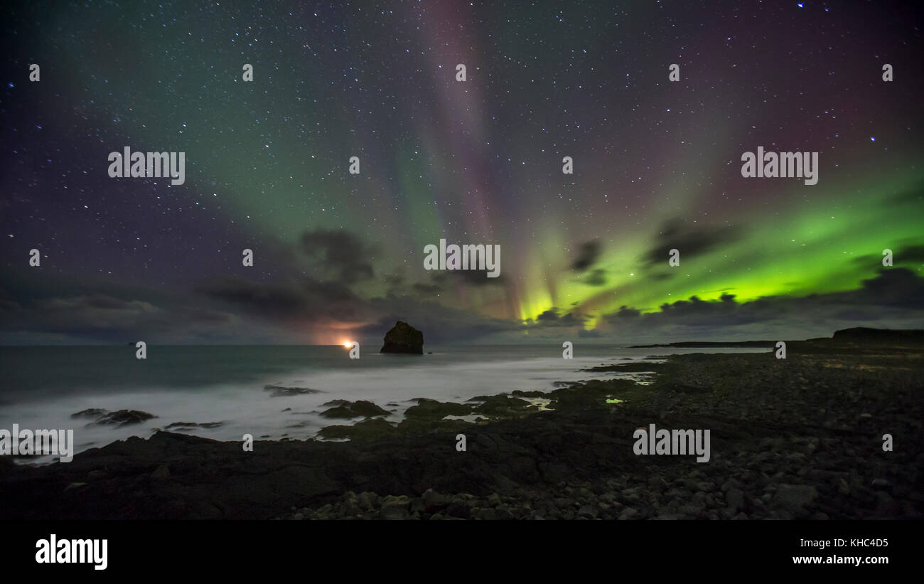 Karlinn sea stack on the Reykjanes peninsula, with northern lights. - Stock Image