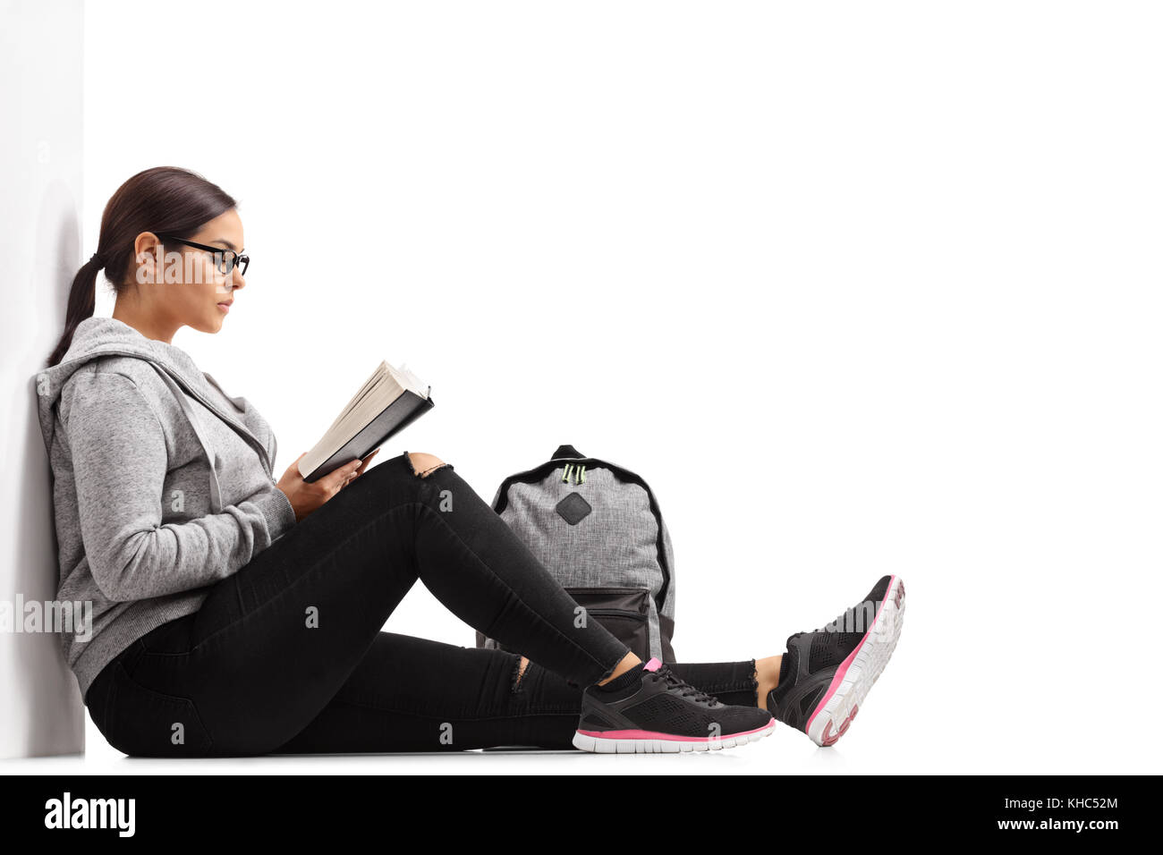 Female Teenage Student Reading A Book And Leaning Against A