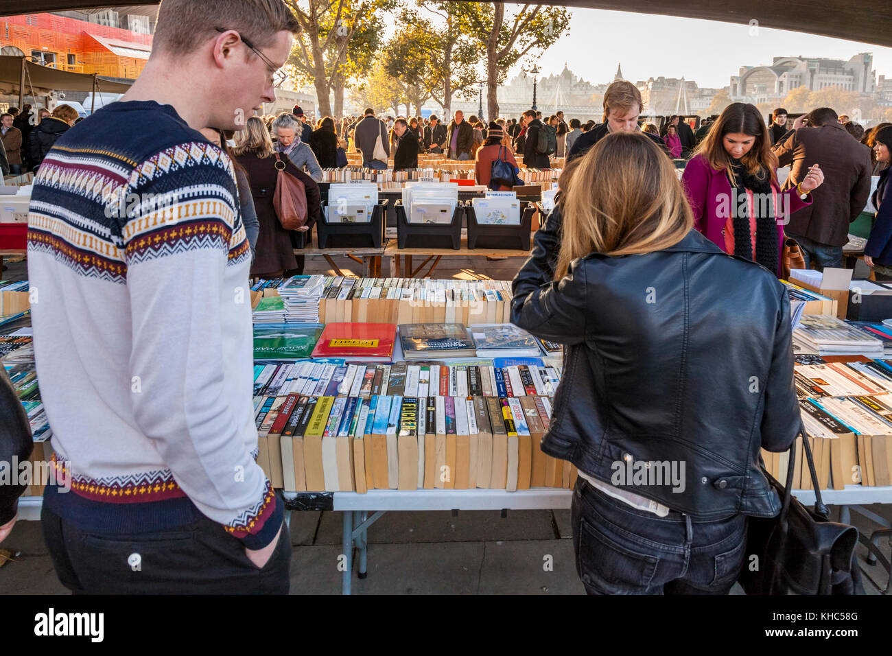 People looking at second hand books for sale at the book market underneath Waterloo Bridge, London, England, UK - Stock Image
