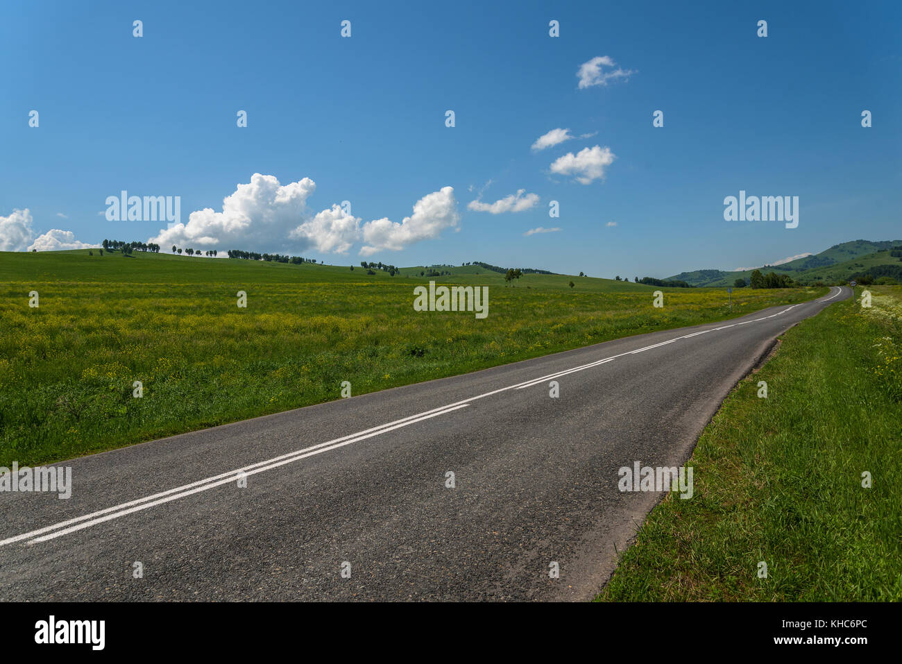Scenic view from the asphalt road among meadows with yellow flowers on a background of mountains and blue sky with Stock Photo